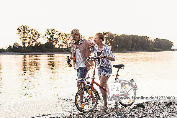 Young couple with bicycle wading in river