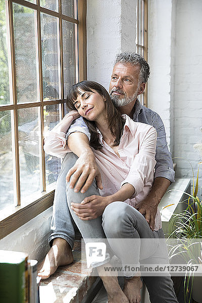 Mature couple sitting on window sill  looking out of window