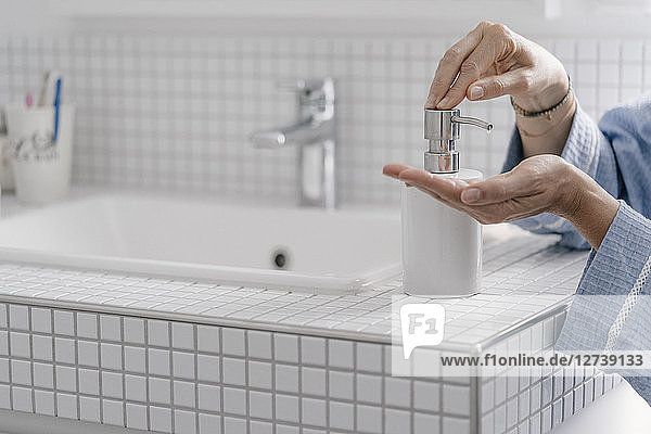 Close-up of woman wputting soap on her hands in bathroom
