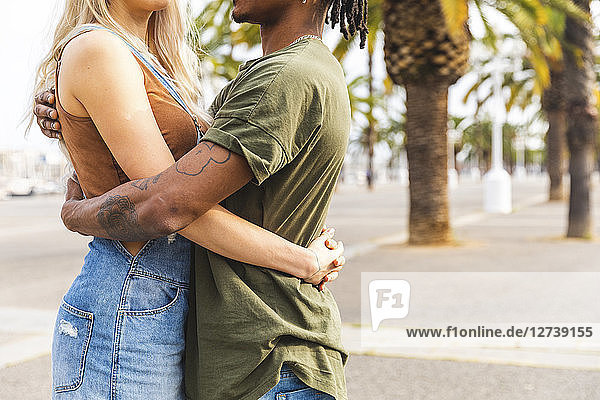 Spain  Barcelona  multicultural young couple embracing on promenade  partial view