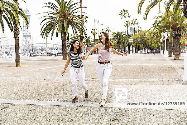 Two happy female friends running on promenade with palms