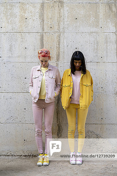 Two alternative friends having fun,  wearing yellow and pink jeans clothes,  looking down