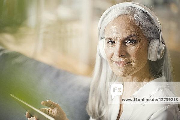 senior woman using digital tablet and headphones