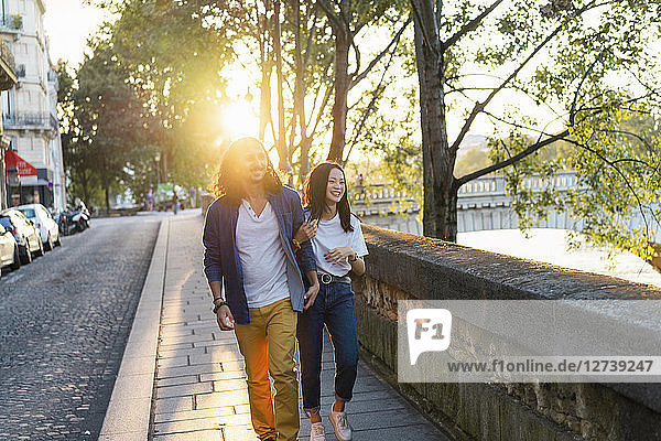 France  Paris  happy young couple walking at river Seine at sunset