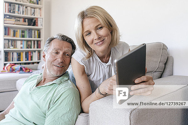 Smiling mature couple at home using tablet