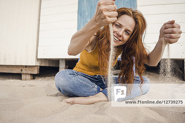 Redheaded woman sitting in front of beach cabin  with sand trickling through her hands