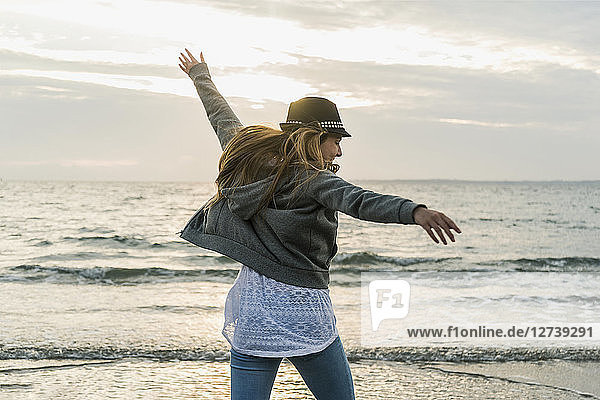 Happy young woman on the beach at sunset