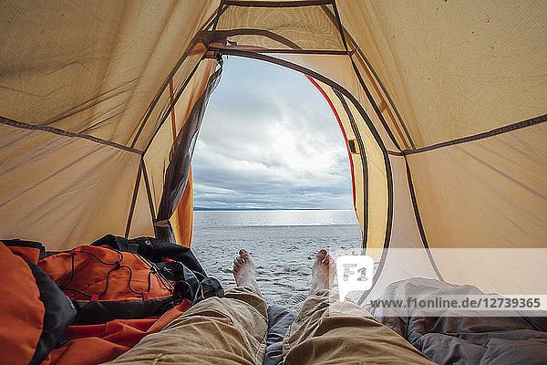 Feet of man  lying in tent on beach