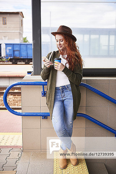 Smiling redheaded woman with coffee to go looking at cell phone at platform