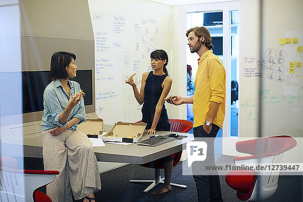 Business people in futuristic office having a meeting  eating pizza