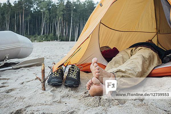 Man lying in tent on beach