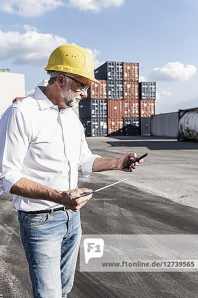 Businessman at cargo harbour  weraing safety helmet  using smartphone and digital tablet