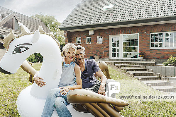 Portrait of smiling mature couple sitting on inflatable pool toy in garden of their home