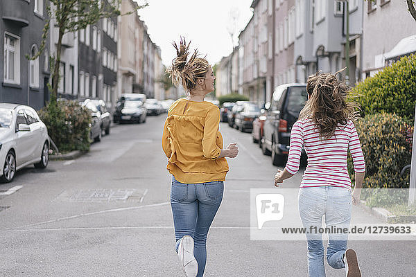 Two girlfriends having fun in the city  running