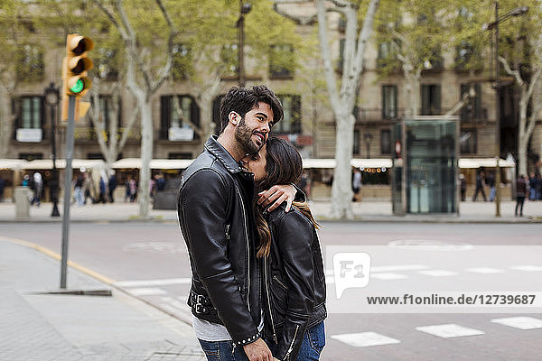 Spain  Barcelona  happy young couple hugging on the street