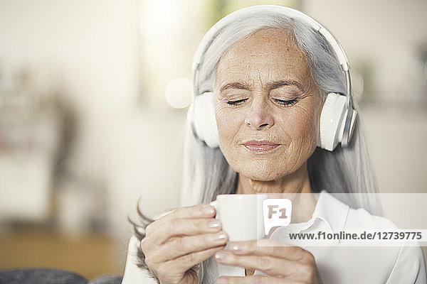 Senior woman listen music with headphones and drinking coffee