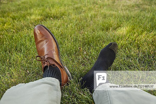 Man's legs and feet - one foot with a shoe and one foot with a sock.