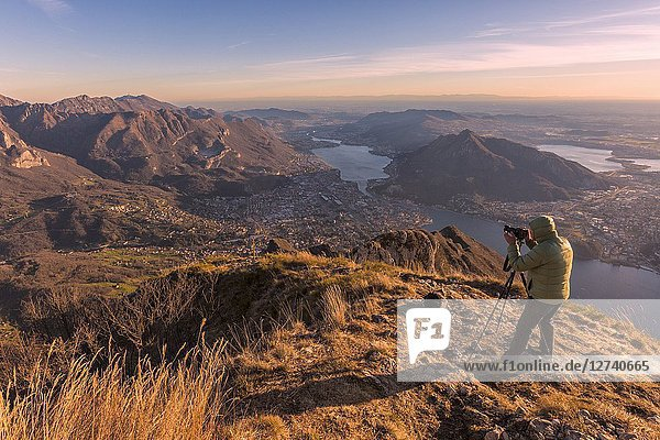 A photographer taking photos of Lecco Lake and Adda river from Coltignone mount at dusk  Lecco Province  lombardy  italy.