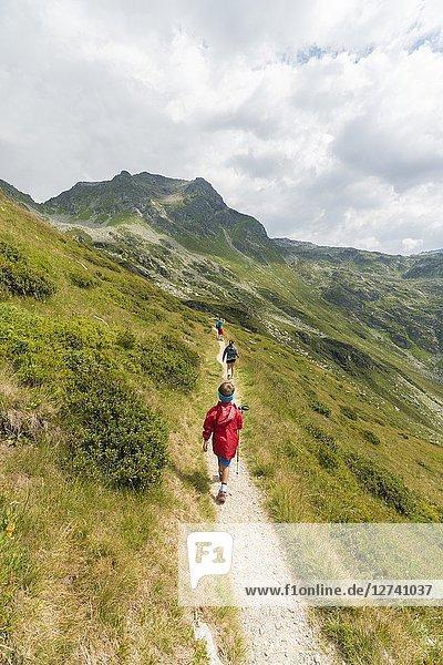 Children walk on footpath towards Lake Emet  Andossi  Spluga Valley  Sondrio province  Valtellina  Lombardy  Italy.