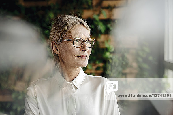 Businesswoman in green office looking out of window
