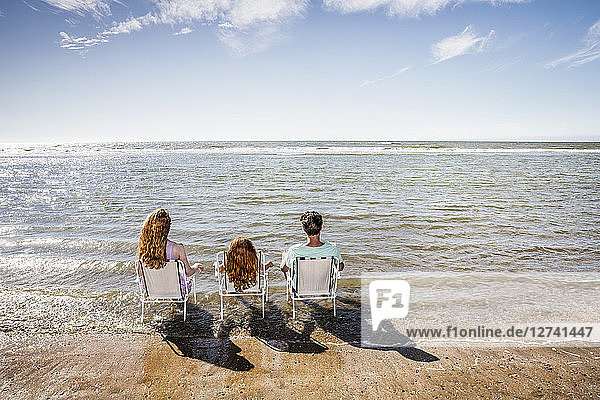 Netherlands,  Zandvoort,  family sitting on chairs in the sea