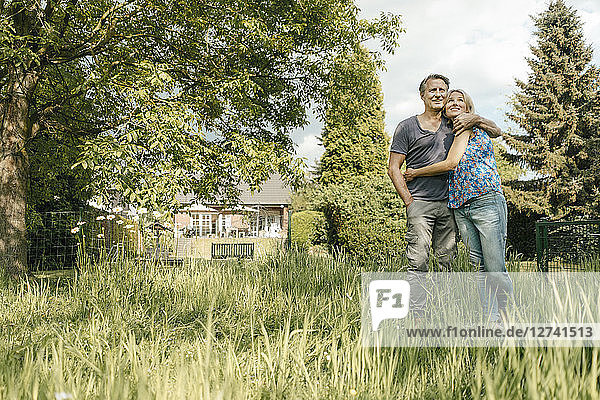 Smiling mature couple embracing in garden of their home