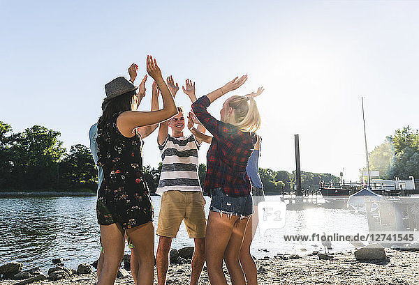 Group of friends raising their hands at the riverside