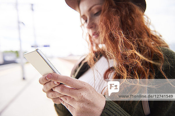 Hans of redheaded woman holding smartphone