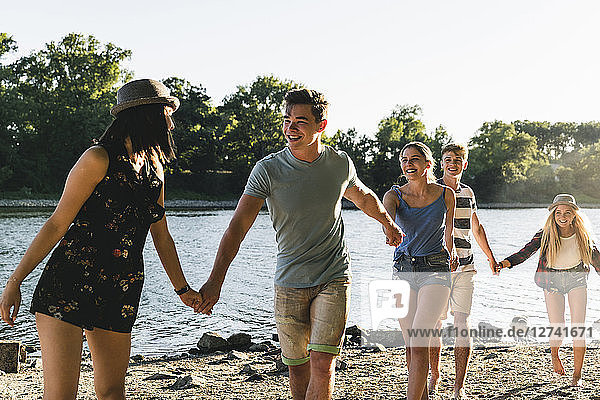 Group of happy friends walking hand in hand at the riverside