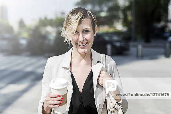 Portrait of smiling businesswoman with Coffee to go