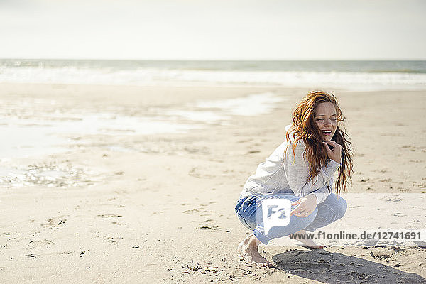 Redheaded woman relaxing on the beach  crouching