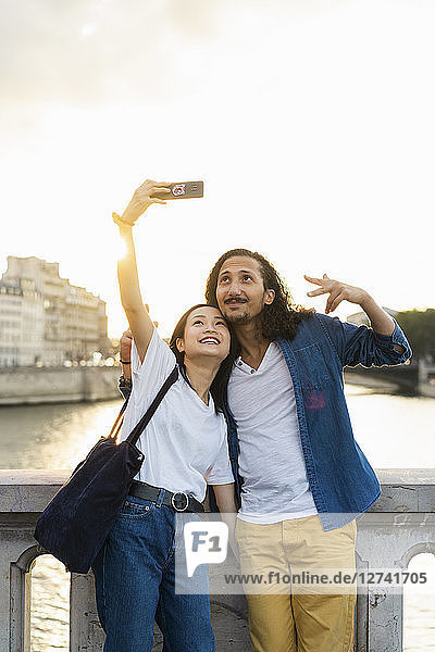 France  Paris  happy young couple taking a selfie at river Seine at sunset