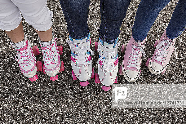 Mother and her two daughters on roller skates  partial view