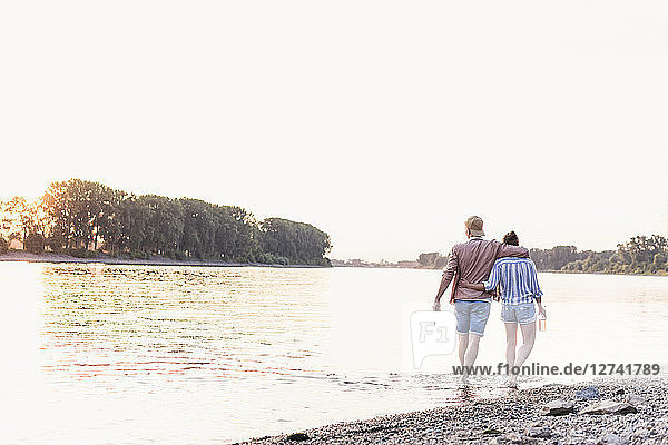 Young couple wading in river at sunset