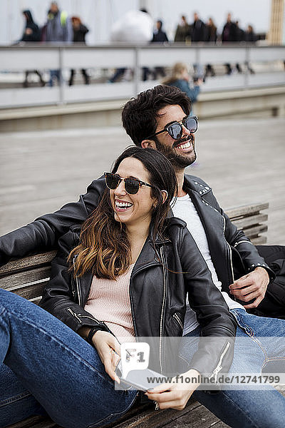 Spain  Barcelona  happy young couple with cell phone resting on a bench