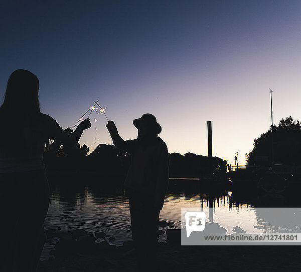 Silhouette of people at the riverside holding sparklers in the evening