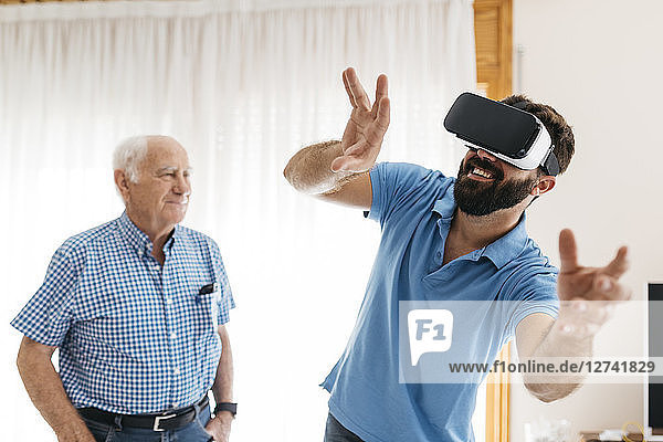 Smiling man using Virtual Reality Glasses at home while his grandfather watching him