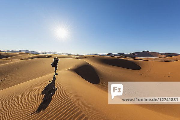Africa,  Namibia,  Namib desert,  Naukluft National Park,  female photograper on sand dune against the sun