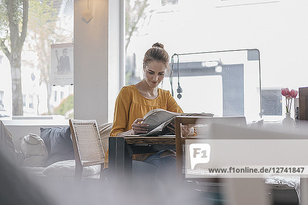 Young woman sitting in coworking space  reading newspaper