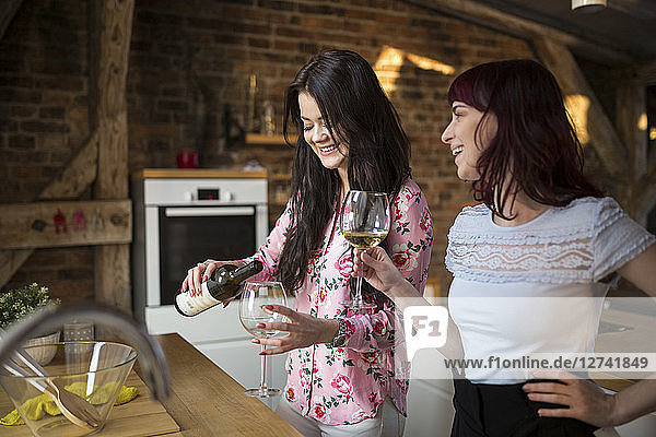 Happy female friends at home drinking white wine