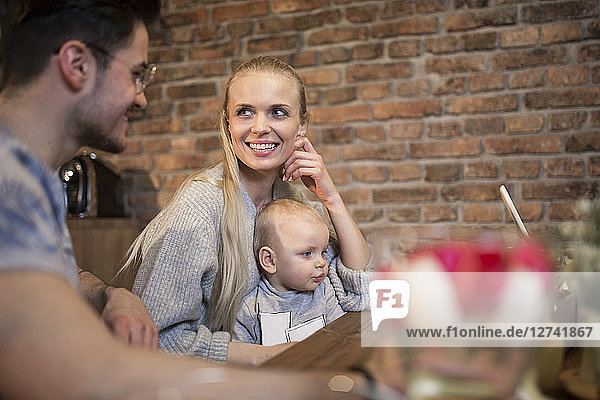 Happy young parents spending time in kitchen at home with their baby girl
