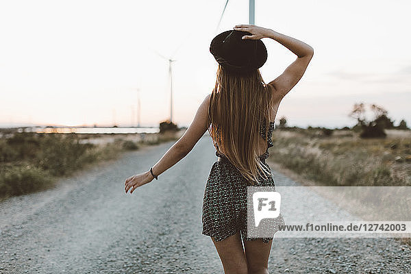 Back view of young woman walking on rural road