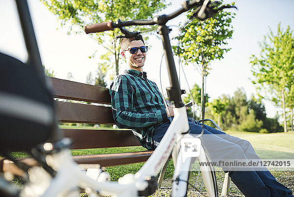 Smiling young man with smartphone on park bench
