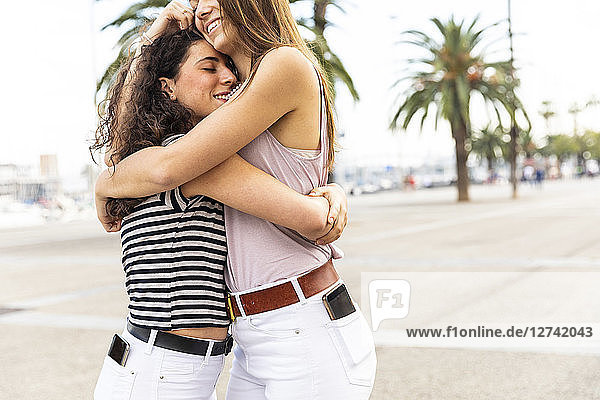 Two happy female friends embracing and hugging on promenade with palms Two happy female friends embracing and hugging on promenade with palms