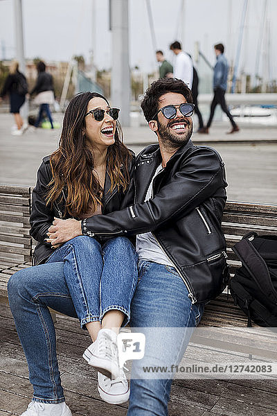 Spain  Barcelona  happy young couple resting on a bench