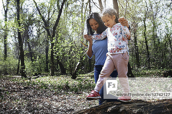 Mother and daughter in park  girl balancing on tree trunk