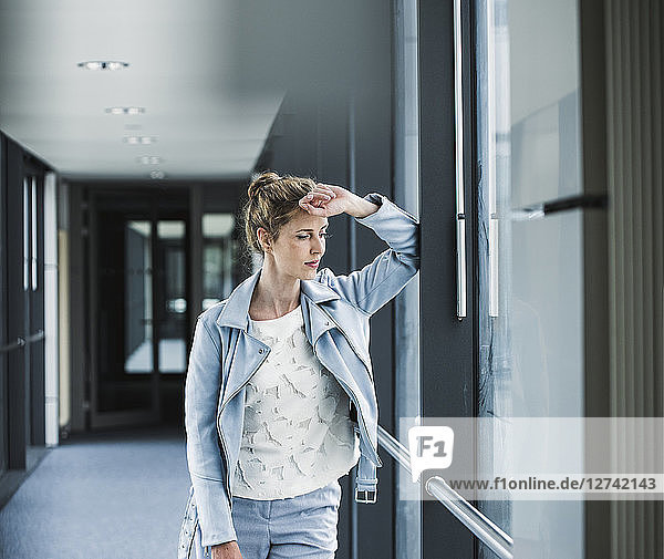 Businesswoman leaning against window in office passageway