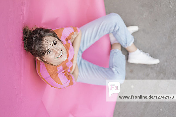 Confident young woman sitting on pink background