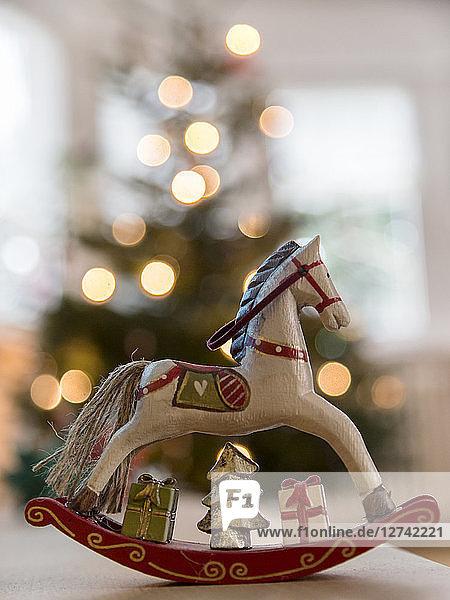 Nostalgic deocrative rocking horse before a lit Christmas tree