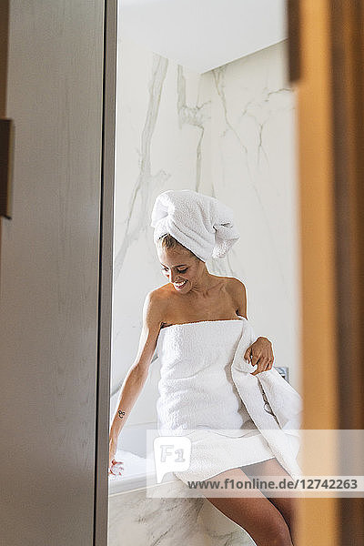 Woman wrapped in towels  sitting on edge of bathtub